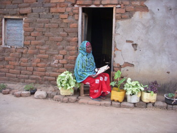 Woman in Tanzania reads while holding a solar-powered lantern purchased from Solar Sister. Solar lanterns, like this one, provide light to women and their families who were previously living in darkness.