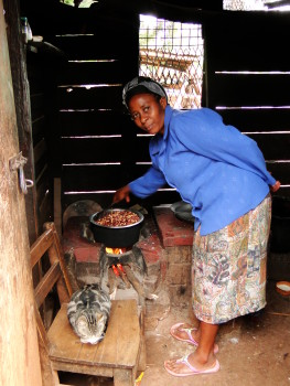 Woman cooks Githeri, a traditional Kenyan dish, over a modified, fixed stove. The stove has been built in a way that will allow it to burn more efficiently and produce less smoke.