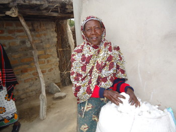 A Solar Sister customer weighs out the cotton she has been able to harvest with the help of her solar lamp. She appreciates the light in her house as well as the decreased danger of her cotton catching fire now that she uses a solar lamp rather than kerosene lamps.