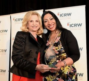 two women posing with an award
